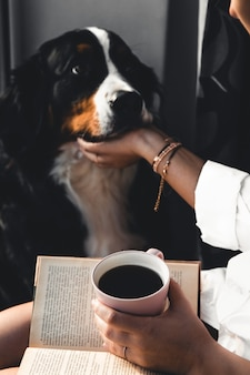 Yoman sitting in living room with her cute bernese mountain dog dog, reading and drinking coffee.