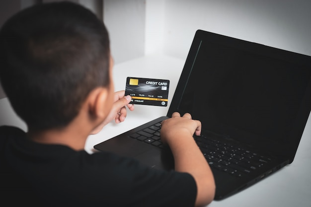 Yong asian children with yellow skin, holding black credit card, black laptop on white table.