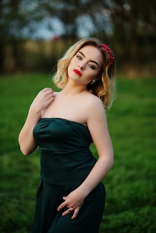 Yong elegant blonde girl at green dress on the garden in spring.