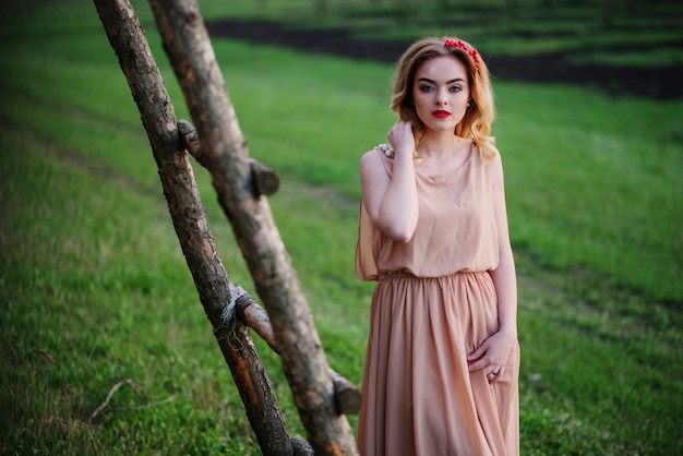 Yong elegant blonde girl at rose dress on the garden background wooden staircase.