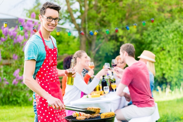 Юн человек у гриля-барбекю переворачивает мясо, на заднем плане друзья устраивают вечеринку в саду
