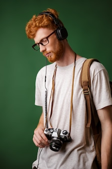 Yong readhead bearded hipster with backpack holding retro camera, listening to music