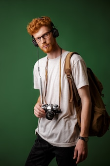 Yong readhead bearded hipster with backpack holding retro camera, listening to music,