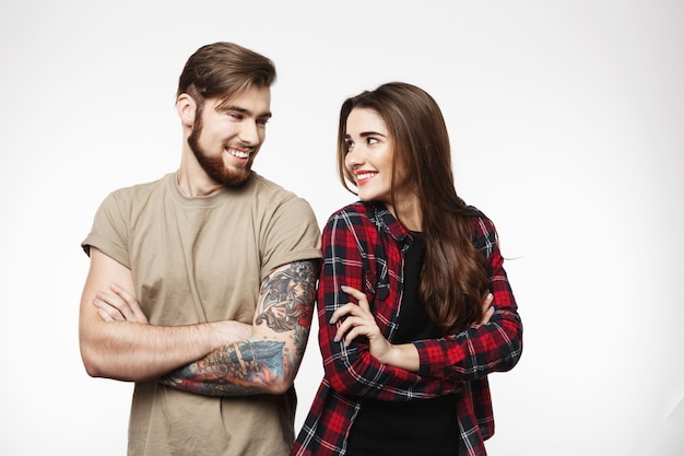 Юн татуированный мужчина и красивая женщина, стоящая скрестив руки.