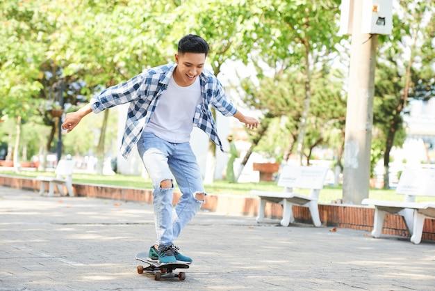 Юн модный человек веселиться со скейтбордом
