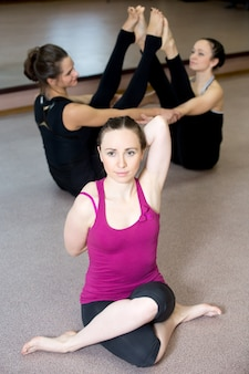 Yong yogi female in sportswear practices yoga asana, gomukhasana
