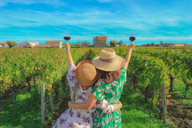 休暇中にブドウ園で赤ワインを飲むyonug女性の裏、パーティーのコンセプト