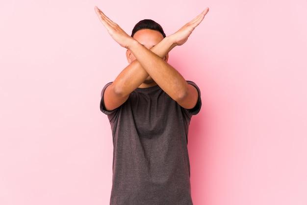 ピンクのウォールキーピング2本の腕を組んでポーズをとるyoラテン男は、拒否の概念。