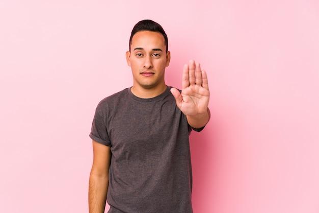 Yooung латинский человек позирует в розовых стенда с протянутой рукой, показывая знак остановки, предотвращая вас.