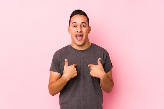 Yooung латинской мужчина позирует на розовый удивлен, указывая пальцем, широко улыбаясь.