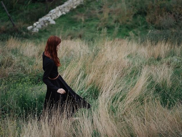あなたは山々の中の草地の乾いた草の上を自然に歩いている黒いドレスを着た女性です