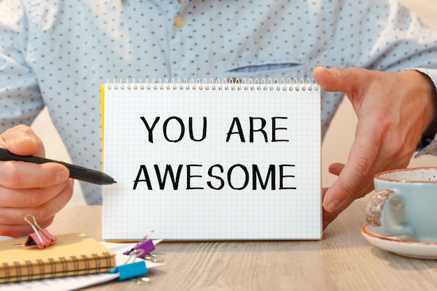 You are awesome is written on a notepad on an office desk with office accessories.