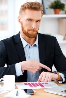 늦었어! 자신의 작업 장소에 앉아있는 동안 카메라를보고 자신의 시계를 가리키는 자신감 수염 사업가