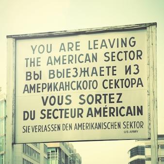 あなたはアメリカのセクターを去ろうとしています-ドイツのベルリンにあるチェックポイントチャーリーの近くの歴史的な看板。レトロなスタイル