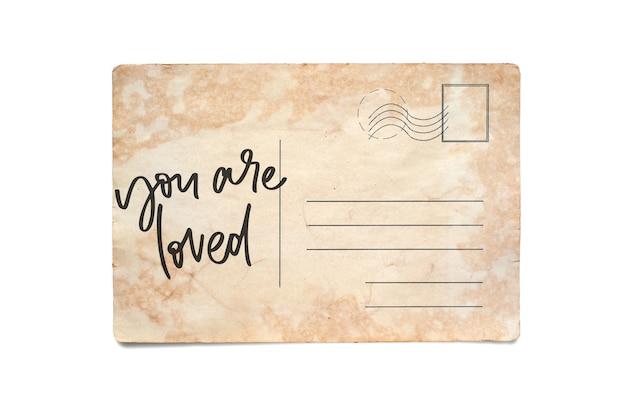 Тебя любят. надпись на старинной открытке. изолированные на белом.