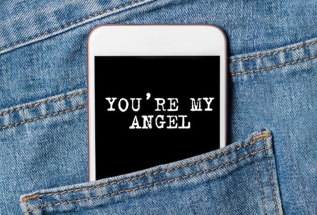 あなたはジーンズの愛とバレンタインの概念のバックグラウンド電話で私の天使です