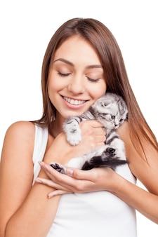 Ты мой маленький пушистый друг! красивая молодая женщина держит маленького котенка в руках и привязывается к нему, стоя на белом фоне