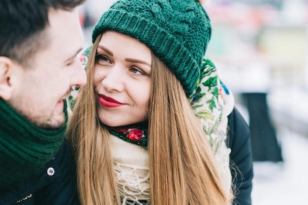 당신은 나의 사랑. 겨울 공원에서 데이트에서 다정한 사랑의 부부. 벤치에 앉아있는 동안 애정으로 그녀의 남자 친구를보고 금발 소녀
