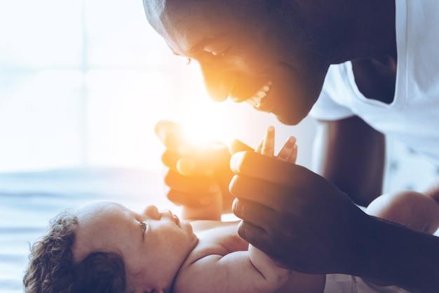 Ты мой мир! вид сбоку счастливого молодого африканца, играющего со своим маленьким ребенком и улыбающегося, лежа в постели