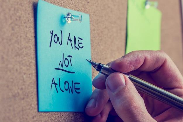 あなたは一人ではありません-万年筆でコルクボードに固定された青い付箋に感動的なメッセージを書いている男性。