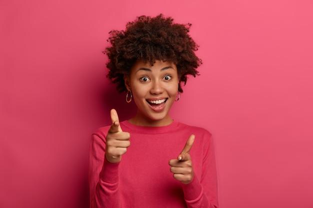 あなたが選ばれました。喜んで陽気でフレンドリーなヒップスターの女の子はアフロの髪型をしていて、指銃のジェスチャーをし、カメラで楽しく示します