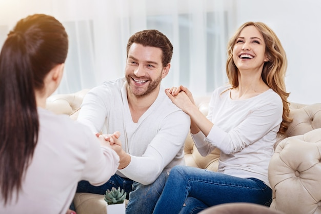 You are the professional. cheerful positive cute couple sitting together and laughing while expressing their gratitude to the psychologist