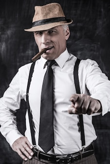 You are the next! serious senior man in hat and suspenders smoking cigar pointing you while standing against dark background