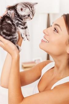Ты такая клевая! красивая молодая женщина держит маленького котенка в руках и смотрит на него с улыбкой