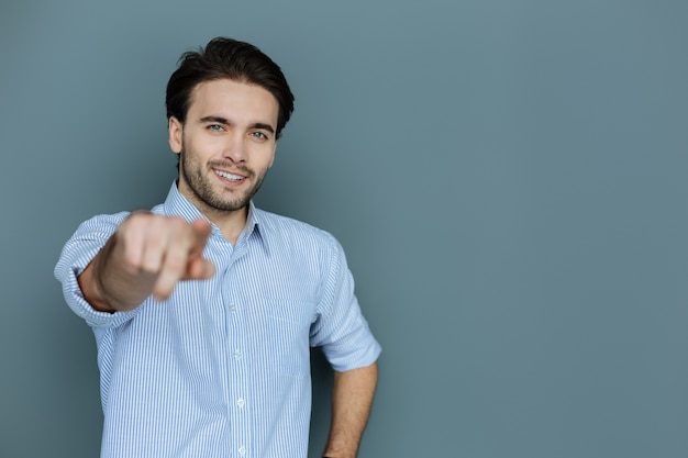 あなたは特別です。あなたを選んでいる間彼の手で微笑んで指さしている素敵なうれしそうなハンサムな男
