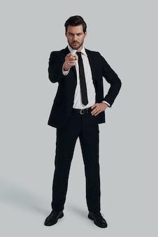 Ты тот, кто мне нужен! красивый молодой человек в полный рост в полном костюме, указывая на вас, стоя на сером фоне