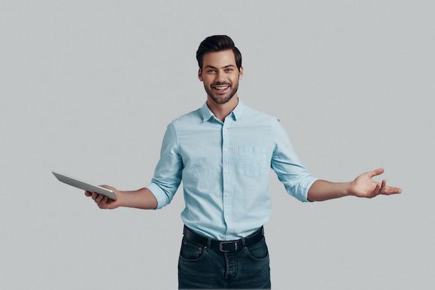 どういたしまして!腕を伸ばしたまま、灰色の背景に立っている間カメラを見ているハンサムな若い男