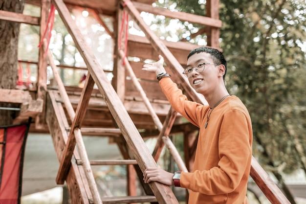 Пожалуйста. позитивный восторженный азиатский мужчина, который держит улыбку на лице и стоит на лестнице