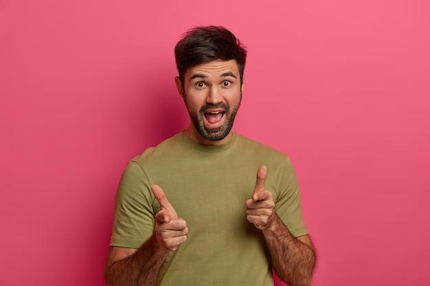 당신은 내가 필요한 것입니다. 손가락 총 제스처로 수염이있는 웃기는 쾌활한 남자, 누군가를 집어 들고, 캐주얼 티셔츠를 입고, 당신이 죽인 뱅이라고 말하고, 활기찬 분홍색 벽 위에 포즈를 취합니다.