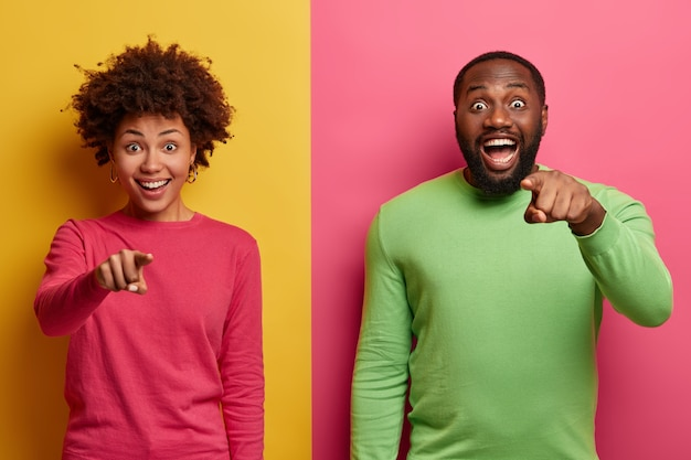 You are what we need. positive surprised afro american woman and man smile broadly and indicate directly at camera, make choice