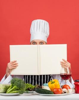 Ты то, что ты ешь. женщина-повар читает поваренную книгу. можно использовать для приготовления пищи. продовольственная студия в ресторане. шеф-повар готовит рецепт. книга рецептов. лучший рецепт. концепция приготовления. работа на современной кухне.