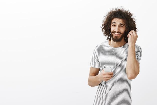 Вы что-то просили. беззаботный счастливый восточный парень в полосатой футболке снимает наушники и улыбается