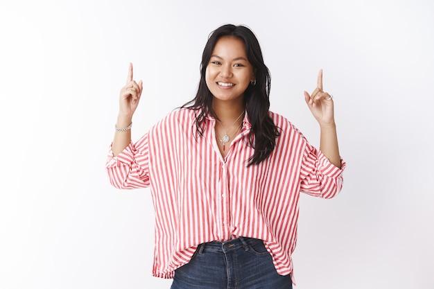 頭を上げた方がいい。熱狂的でのんきな若いアジアのかわいい女の子の肖像画は、ストライプのブラウスでのんびりと笑顔で上向きに手を上げて招待し、興味深いプロモーションを参照してください