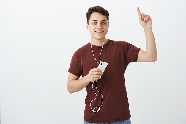 고개를 들어 올리는 것이 좋습니다. 이어폰에 긍정적 인 매력적인 남성 고객의 초상화