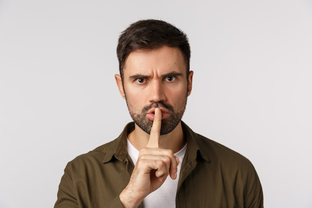 You better stay quiet about this. aggressive, angry, displeased caucasian bearded male in coat, shushing demand keep silent, hushing with index finger press lips, frowning bothered, white background