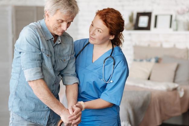 넌 더 잘할 수있어. 성숙한 신사에게 부상에서 회복하는 동안 큰 진전을 이루고 있다고 말하는 친절하고 근면 한 의료 종사자