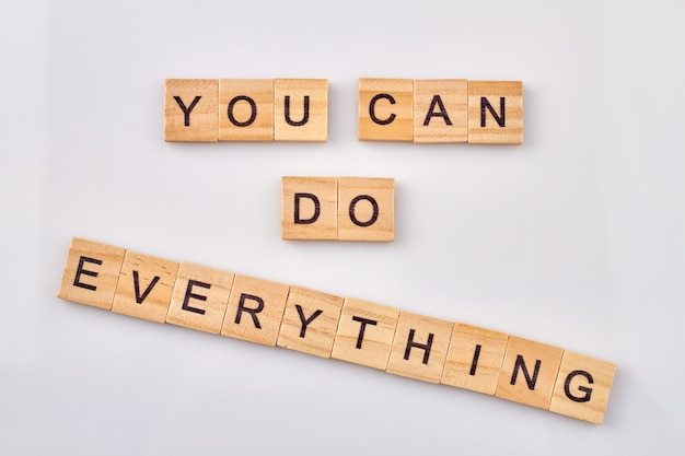 あなたはすべてを行うことができます。自己信念のためのやる気を起こさせる言葉。白い背景の上の木製の立方体。