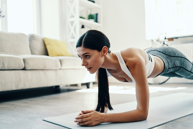 You can do it! beautiful young woman in sports clothing keeping plank position while spending time at home