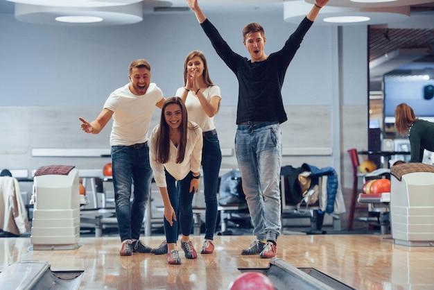 Puoi fare lo sciopero. i giovani amici allegri si divertono al bowling durante i fine settimana
