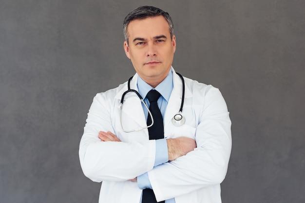 Вы можете положиться на этого врача. зрелый мужчина-врач держит скрещенными руками и смотрит в камеру, стоя на сером фоне