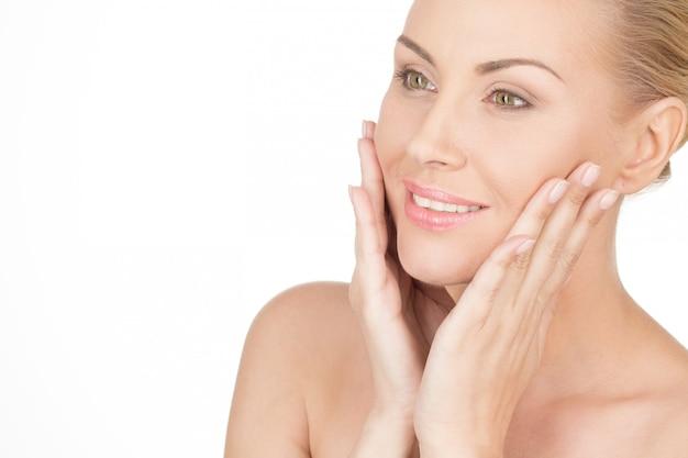 あなたは彼女が彼女の肌を愛していると言うことができます。完璧な肌を持つ美しい成熟した女性のクローズアップショット Premium写真