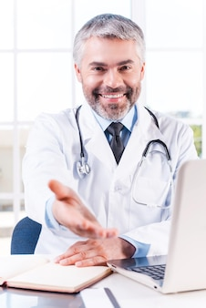 날 믿어도 돼! 자신의 작업장에 앉아 손을 뻗어 웃고 있는 자신감 있는 성숙한 회색 머리 의사