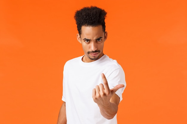 You come here now. serious bossy and strict, confident man with angry expression, frowning looking under forehead and flick index finger as if inviting, demand person step foward, orange wall