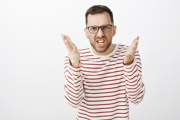 귀머거리거나 멍청하거나 미워합니다. 분노에서 찡그린 얼굴을하고 싸우는 동안 뭔가를 설명하면서 손바닥을 흔드는 분노한 스트레스 수염 남자의 초상화