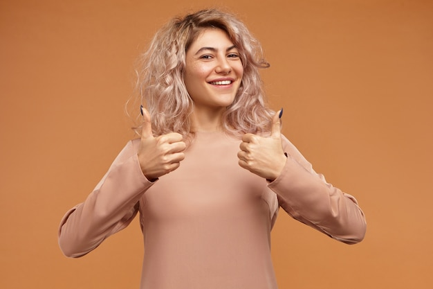 Вы хорошо поработали! уверенная в себе успешная молодая женщина со стильной прической широко улыбается, показывает палец вверх обеими руками, говорит: