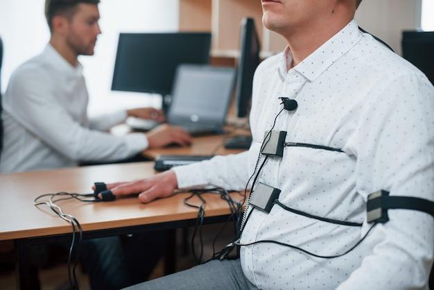 Вы не знали, что думает ваш коллега. подозрительный мужчина проходит детектор лжи в офисе. задавать вопросы. проверка на полиграфе